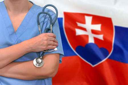 Female surgeon or doctor with stethoscope in hand on the background of the Slovakia flag. Surgery concept in Slovakia