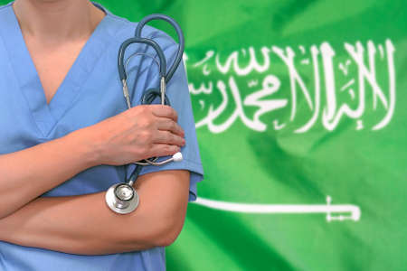 Female surgeon or doctor with stethoscope in hand on the background of the Saudi Arabia flag. Surgery concept in Saudi Arabia
