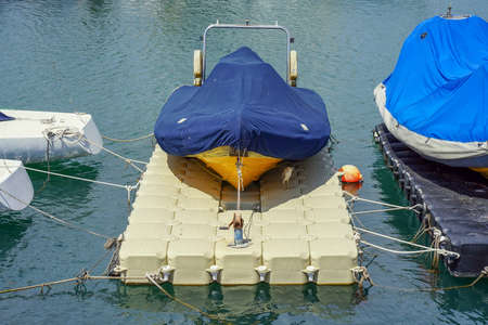 Small motor boat at anchor by rope in pier Standard-Bild