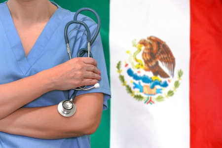 Female surgeon or doctor with stethoscope in hand on the background of the Mexico flag. Surgery concept in Mexico Foto de archivo