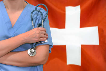 Female surgeon or doctor with stethoscope in hand on the background of the Switzerland flag. Surgery concept in Switzerland