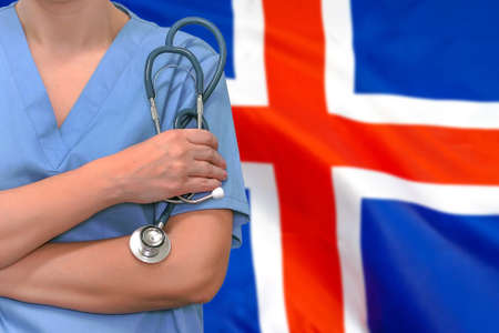 Female surgeon or doctor with stethoscope in hand on the background of the Iceland flag. Surgery concept in Iceland