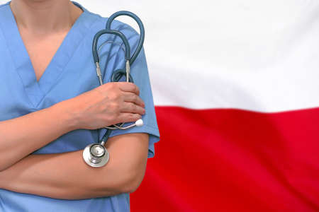 Female surgeon or doctor with stethoscope in hand on the background of the Poland flag. Surgery concept in Poland Foto de archivo