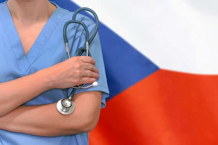 Female surgeon or doctor with stethoscope in hand on the background of the Czech Republic flag. Surgery concept in Czech Republic