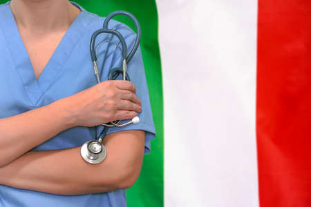 Female surgeon or doctor with stethoscope in hand on the background of the Italy flag. Surgery concept in Italy