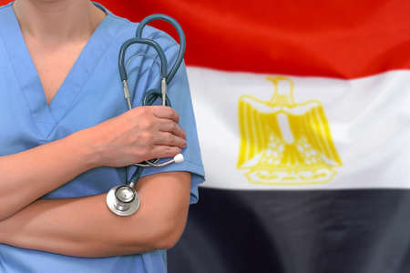 Female surgeon or doctor with stethoscope in hand on the background of the Egypt flag. Surgery concept in Egypt
