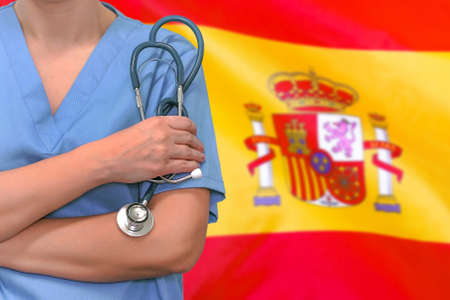 Female surgeon or doctor with stethoscope in hand on the background of the Spain flag. Surgery concept in Spain Foto de archivo