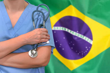 Female surgeon or doctor with stethoscope in hand on the background of the Brazil flag. Surgery concept in Brazil