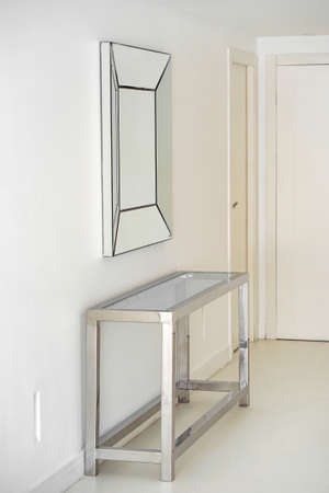 Stainless steel table and abstract mirror in hall. Entrance hall of contemporary family home