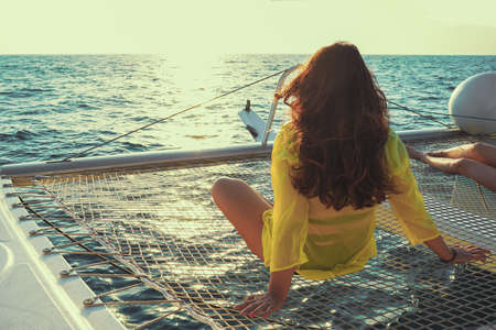 Woman sits on the deck of a sailing catamaran at sunset in the sun. Rear view of a woman enjoying the azure water on the deck of a sailing yacht. Selective focus, blur