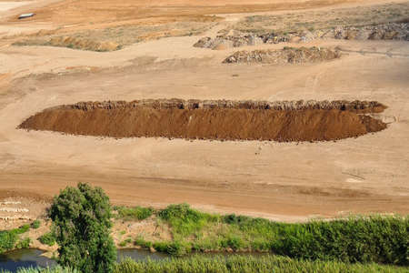 A large pit dug in the field. Large pit. Deep sand pit dug for trash in the field. House construction concept