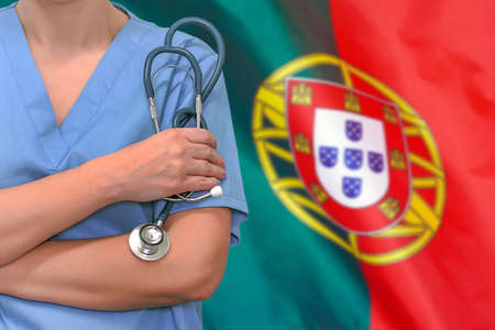Female surgeon or doctor with stethoscope in hand on the background of the Portugal flag. Surgery concept in Portugal