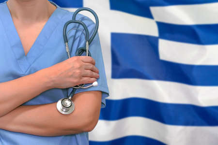 Female surgeon or doctor with stethoscope in hand on the background of the Greece flag. Surgery concept in Greece