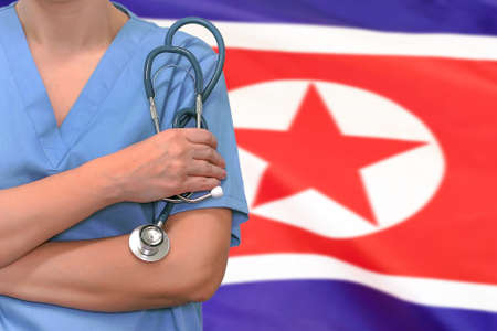Female surgeon or doctor with stethoscope in hand on the background of the North Korea flag. Surgery concept in North Korea Foto de archivo