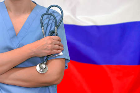 Female surgeon or doctor with stethoscope in hand on the background of the Russia flag. Surgery concept in Russia