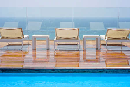 Three loungers, standing and table on a wooden floor on the background of the sea