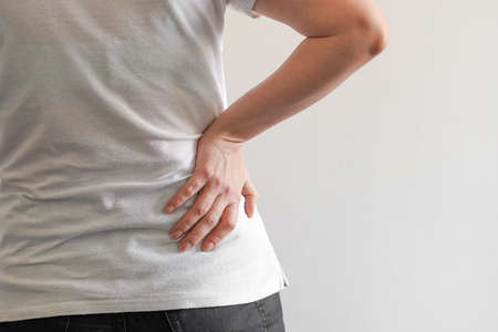 Woman suffer from low back pain. Hand of woman holding her waist backache in pain. Health care concept. Stock Photo