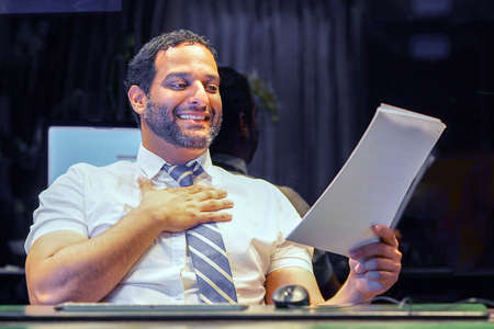 Happy man, enjoying the good news in writing. An euphoric male is happy after reading good news in a written letter, approving a loan, raising her job.