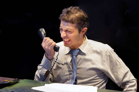 Angry office worker yells on phone. Aggressive boss yelling into telephone receiver to one of his employees Stock Photo