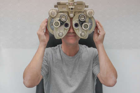 Male checks his vision on the machine checking patient vision at eye clinic or optics store. Face closeup. Stock Photo