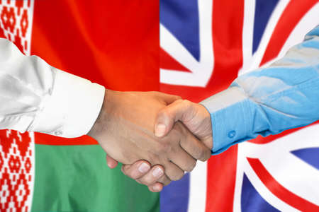 Business handshake on the background of two flags. Men handshake on the background of the Belarus and UK flag. Support concept.