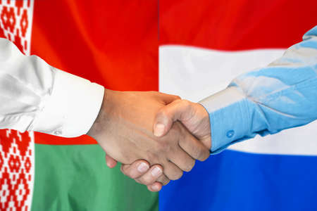 Business handshake on the background of two flags. Men handshake on the background of the Belarus and Netherlands flag. Support concept.