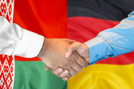 Business handshake on the background of two flags. Men handshake on the background of the Belarus and Germany flag. Support concept.