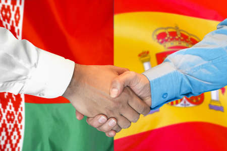 Business handshake on the background of two flags. Men handshake on the background of the Belarus and Spain flag. Support concept.