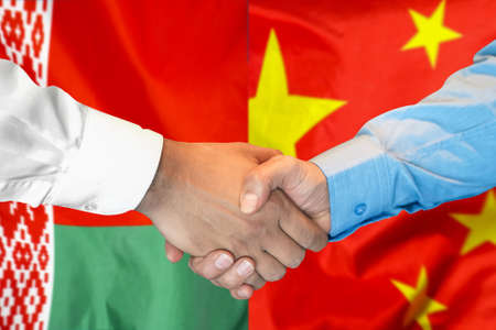 Business handshake on the background of two flags. Men handshake on the background of the Belarus and China flag. Support concept.