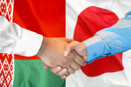Business handshake on the background of two flags. Men handshake on the background of the Belarus and Japan flag. Support concept. Stock Photo