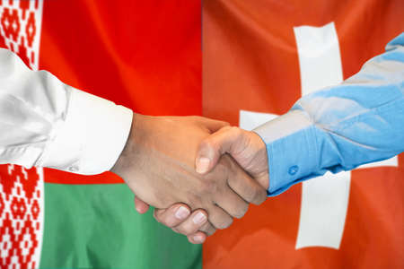 Business handshake on the background of two flags. Men handshake on the background of the Belarus and Switzerland flag. Support concept. Stock Photo