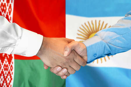 Business handshake on the background of two flags. Men handshake on the background of the Belarus and Argentina flag. Support concept.