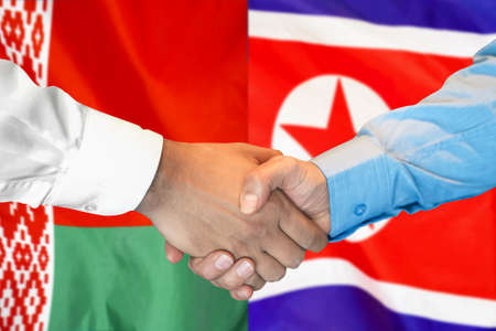 Business handshake on the background of two flags. Men handshake on the background of the Belarus and North Korea flag. Support concept.