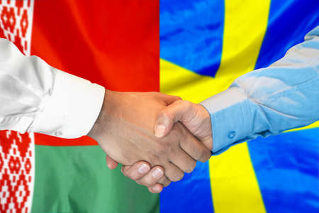 Business handshake on the background of two flags. Men handshake on the background of the Belarus and Sweden flag. Support concept. Stock Photo
