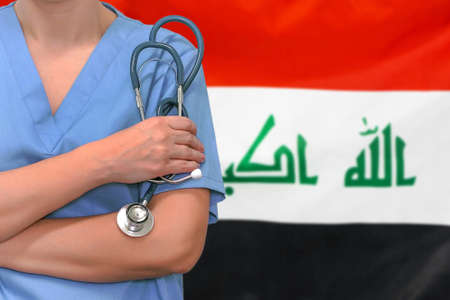 Female surgeon or doctor with stethoscope in hand on the background of the Iraq flag. Surgery concept in Iraq