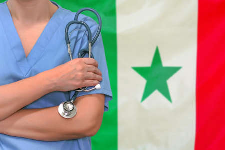Female surgeon or doctor with stethoscope in hand on the background of the Senegal flag. Surgery concept in Senegal Reklamní fotografie