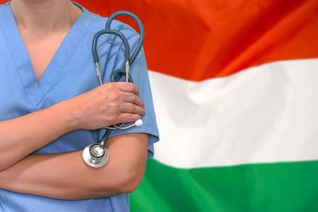 Female surgeon or doctor with stethoscope in hand on the background of the Hungary flag. Surgery concept in Hungary