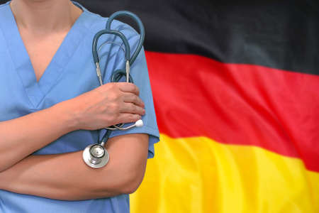Female surgeon or doctor with stethoscope in hand on the background of the Germany flag. Surgery concept in Germany 免版税图像 - 164527931