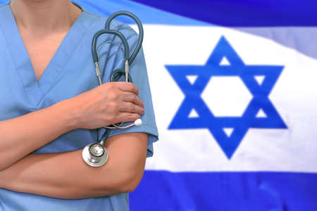 Female surgeon or doctor with stethoscope in hand on the background of the Israel flag. Surgery concept in Israel 免版税图像