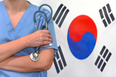 Female surgeon or doctor with stethoscope in hand on the background of the South Korea flag. Surgery concept in South Korea 免版税图像