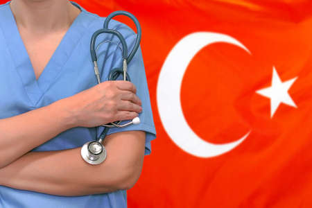 Female surgeon or doctor with stethoscope in hand on the background of the Turkey flag. Surgery concept in Turkey 免版税图像