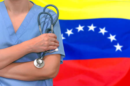 Female surgeon or doctor with stethoscope in hand on the background of the Venezuela flag. Surgery concept in Venezuela