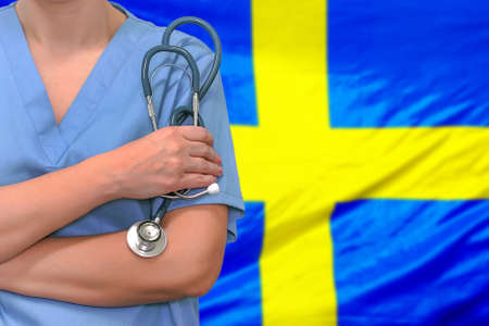 Female surgeon or doctor with stethoscope in hand on the background of the Sweden flag. Surgery concept in Sweden
