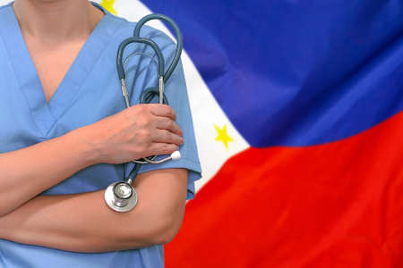 Female surgeon or doctor with stethoscope in hand on the background of the Philippines flag. Surgery concept in Philippines Stock Photo