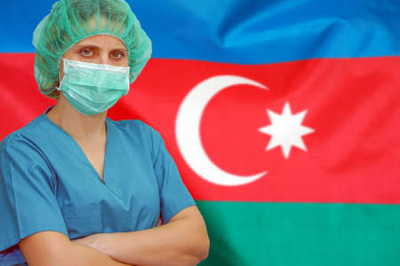 Female surgeon in mask and hat looks at the camera on the background of the Azerbaijan flag. Health care and medical concept. Surgery concept and fight the virus in Azerbaijan