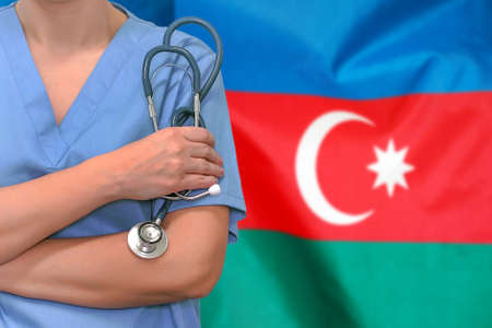 Female surgeon or doctor with stethoscope in hand on the background of the Azerbaijan flag. Surgery concept in Azerbaijan