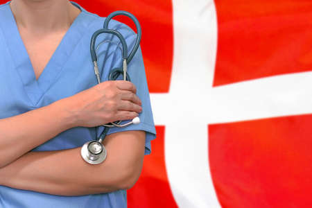 Female surgeon or doctor with stethoscope in hand on the background of the Denmark flag. Surgery concept in Denmark Stock Photo