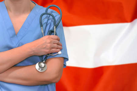 Female surgeon or doctor with stethoscope in hand on the background of the Austria flag. Surgery concept in Austria