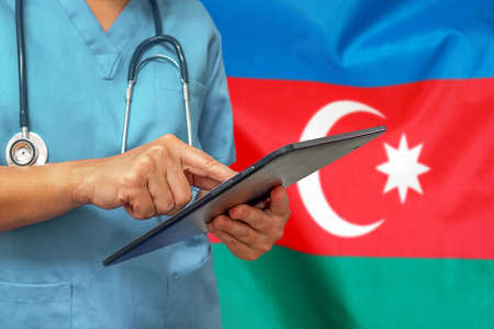 Surgeon or doctor using a digital tablet on the background of the Azerbaijan flag. Medical equipment or medical network, technology and diagnostics in Azerbaijan 免版税图像