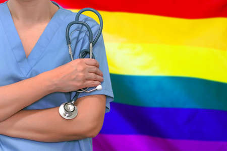 Female surgeon or doctor with stethoscope in hand on the background of the rainbow flag LGBT